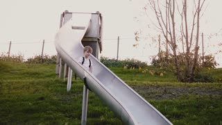 Little boy goes down very slowly on sliding board. Slow motion. Cute male child looking at camera on green playground.
