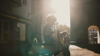 Little boy on a playground horse spring rider. Cute European kid having fun with a teddy bear outside in the morning. 4K