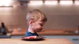 Little boy sitting at the table, turns the head and sees watermelon on a plate. Male shout of joy and take a bite.