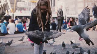 Little Caucasian girl feeds birds outside. Slow motion. Happy female kid feeding pigeons on crowded sunny city square.