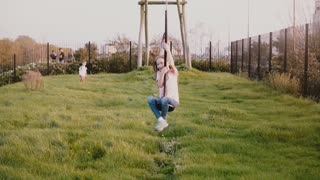 Little Caucasian girl on a city park zipline. Slow motion. Excited happy female child riding a long zip wire, smiling.