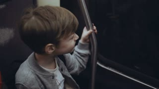Little cute boy traveling through the city buy subway. Smiling young male hold on to the handrail and looking at window.