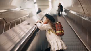 Little cute girl going upstairs by escalator in subway. Beautiful female child clothing in french style with backpack.