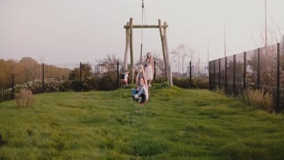 Little European girl on a playground zip wire. Slow motion. Happy female child rides a long zipline swing. Childhood.