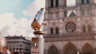 Little girl in beret using coin-operated telescope. Slow motion. Notre Dame de Paris. Stationary binoculars. Vacation.