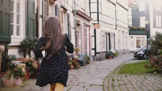 Little girl in black dress running on old road. Back view slow motion. Half-timbered houses. Happy carefree childhood.