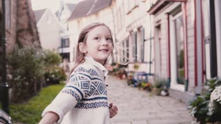 Little girl looks at camera, runs on paved road. Back view. Slow motion. Cute European child running in old street.