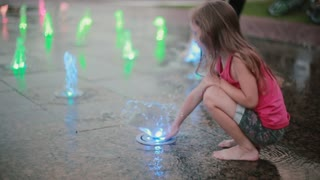 Little girl playing with colored water jets at fountain. Child touching flow with her hand, stands on a water jet.