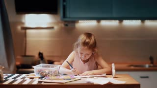 Little girl sitting at the table and drawing with colored pen in large room with soft light. Touching nose.