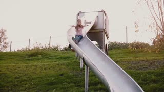 Little happy girl goes down a sliding board. Slow motion. Cute female child with long hair on summer green playground.