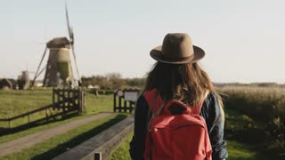Local girl slowly walks up to a windmill farm. Woman in hat with long hair and red backpack coming back home. 4K.