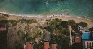 Lockdown aerial shot of exotic ocean coast resort houses with palm trees, waves washing lovely beach on a sunny day.