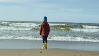 Lonely little girl in bright yellow rubber boots standing on the sandy beach and resting. Cute female looks at the waves