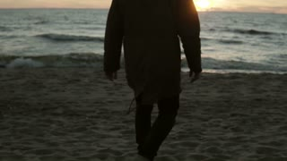 Lonely man walking on the shore of the sea and enjoying the sunset. Young male admires the waves on the beach.