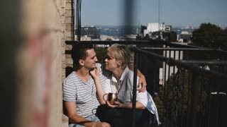 Lovely multiethnic romantic couple sitting barefoot close together, talking, kissing gently at a lovely sunny balcony.