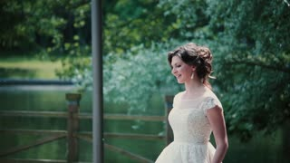 Loving couple meet on their wedding day. Beautiful bride comes up to her groom, he turns to her, they smile and kiss.