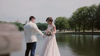 Loving couple on a quay. Beautiful bride shows her wedding dress, swirls around. Happy lovers laugh and enjoy happy day.