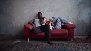 Loving multiracial couple on the red sofa. Woman playing with man s palm, hold hands and laught. Slow motion.