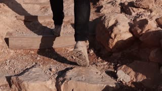 Male legs climbing up on desert stairs. Slow motion. Man steps on desert rocky hill. Back view. Stepping up. Career path