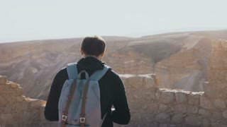 Male photographer walks along ancient Israel ruins. Road to Masada fortress. Young man with backpack takes photos. 4K.