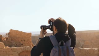 Male tourist photographs amazing mountain scenery. Young man with backpack takes photos. Freedom. Masada Israel 4K.