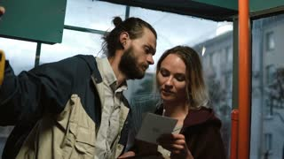 Man and woman holding the card from box and reading something. Young couple in hugging in tram in evening.