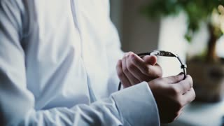 Man in a white shirt puts on a watch. Young businessman getting ready at the morning. Close-up view of male hands.
