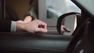 Man paying credit card for buying inside car, enters a PIN code. Close-up view of businessman hand from the car window.
