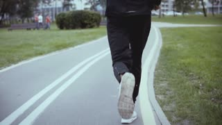 Man running along a city park road. Slow motion. Back view. Tilt up. Successful businessman jogging on a green alley.