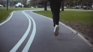 Man running along a winding park road. Back view. Slow motion. Sportsman in white sneakers jogging on a quiet alley.