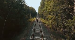 Man running between the rail lines. Drone back view. Athlete rushing to new perspective on autumn forest railroad.