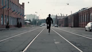 Man running fast in the middle of an old street. Real time shot. Freedom. Camera follows sportsman between tram tracks.