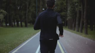 Man running fast on a park road. Real time shot. Back view. Freedom and energy. Camera follows sportsman working out.