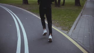 Man running on autumn park road turn. Back view. Slow motion. Sportsman jogging on peaceful quiet alley. Rhythm of life.