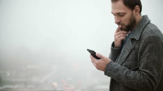 Man standing against the of Eiffel tower in Paris, France in foggy day. Handsome male using smartphone with touchscreen.