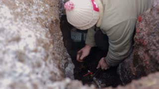 Man standing in a hole in the earth and making repair of water system. Plumber with spanned installing a faucet.