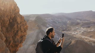 Man takes photos of amazing desert landscape. European male tourist with camera at massive mountain view. Israel 4K.