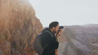 Man takes photos of massive mountain scenery. Caucasian male with camera photographs and looks at his camera. Israel 4K.