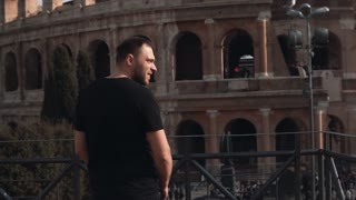 Man tourist visiting Rome, Italy, considers sights in the city, turns back and takes photos of Colosseum. Slow motion.