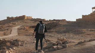 Man with backpack hiking among ancient ruins. Relaxed European male traveler walks on desert rocks and sand. Israel 4K.