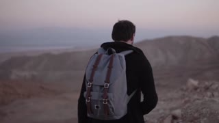 Man with backpack hitchhikes in dusk desert. Slow motion. Caucasian male with smartphone autostops near a sunset highway