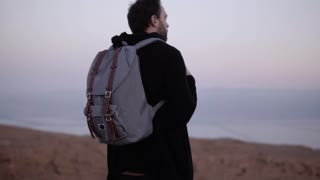 Man with backpack standing alone in dusk desert. Slow motion. Traveler looking at sunset sky. Searching for inspiration.