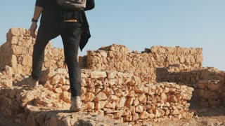 Man with backpack steps on ancient walls ruins. Caucasian male tourist hikes on big yellow rocks. Israel Masada 4K.