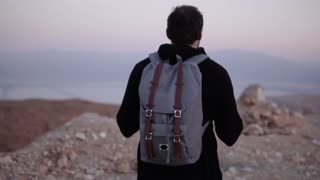 Man with backpack walking in dusk desert wilderness. Slow motion. Male wanders alone looking at scenic sunset sky.