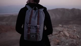 Man with backpack walks alone in dusk desert. Slow motion. Amazing sunset mountains scenery. Searching for inspiration.