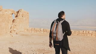 Man with backpack walks on desert mountain top. Casual journalist blogger takes photos of Dead Sea scenery. Israel 4K.
