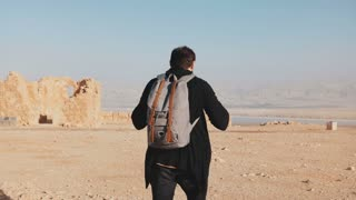 Man with backpack walks on desert mountain top. Relaxed European male tourist enjoys Dead Sea panorama. Israel 4K.