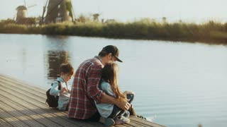 Man with two kids sit together on small lake pier. Single dad in black baseball cap. Family spends time outdoors. 4K.