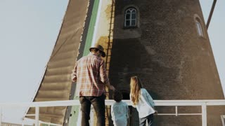 Man with two kids stand by old Dutch windmill. Single father with daughter and son look at a huge mill. Back view. 4K.