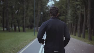 Man working out in a park. Slow motion. Back view. Fit sportsman jogging on a forest alley. Camera tilt down shot.
